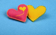 Two felt craft hearts, pink and yellow on blue - stock photo
