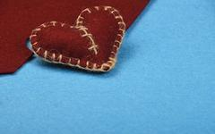 Felt craft and art brown heart cut out on blue Stock Photos