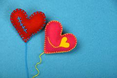 Two felt craft art hearts, pink and red on blue - stock photo