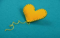 Felt craft and art yellow heart, thread on blue - stock photo
