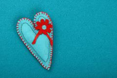 Felt craft and art teal heart with flower on blue Stock Photos