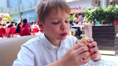 Child eating a bun with a Patty and cheese Stock Footage