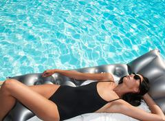 Woman tanning on air bed by the pool Stock Photos