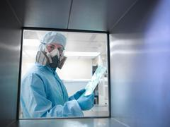 View through hatch at scientist in full protective clothing and mask, in clean Stock Photos