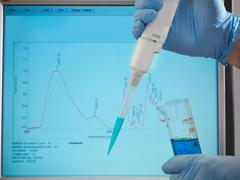 Hands in surgical gloves hold a sample of blue liquid and a pipette in front of Stock Photos