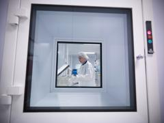 View through clean room hatch, of female scientist working with product in an Stock Photos