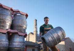 Worker carrying barrel outside brewery Stock Photos