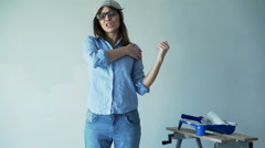 Hipster woman having shoulder pain while painting wall at her new home Stock Footage