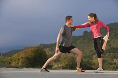 Young athletic couple stretching - stock photo