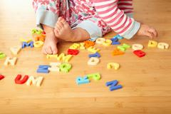 Close up of girl playing with letters - stock photo