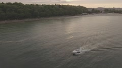 Smooth aerial RAW shot of motorboat, coast, sunset(3) Stock Footage