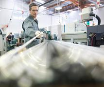 Male engineer working with metal rods on factory floor, surrounded by machinery - stock photo