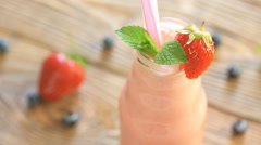 Strawberry shake in glass jar on the wooden table Stock Footage