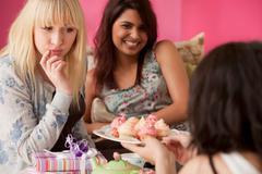 Three young women having a tea party - stock photo