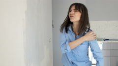 Young woman having shoulder pain while painting wall at her new home Stock Footage