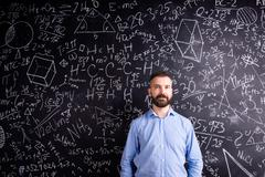 Hipster teacher against big blackboard with mathematical symbols - stock photo