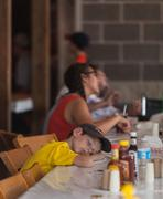 DES MOINES, IA /USA - AUGUST 10,2014: tired boy rests head on table at the Iowa  Kuvituskuvat