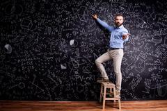 Man writing on big blackboard with mathematical symbols Stock Photos