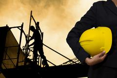 engineer holding Yellow helmet - stock photo