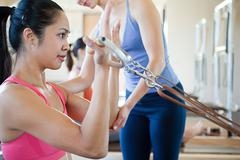 Woman doing bicep curls in pilates Stock Photos