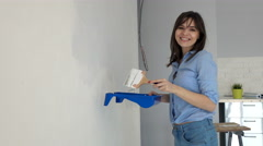 Portrait of happy, pretty woman painting wall at her new home Stock Footage