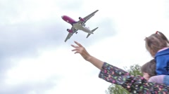 Woman with a child on shoulders joyfully greeted the plane landing near airport Stock Footage