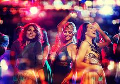 happy friends dancing in club with holidays lights - stock photo