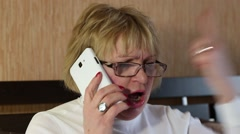 Angry woman communicates via smartphone Stock Footage