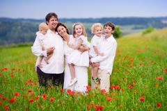 Family with four kids in poppy flower field - stock photo