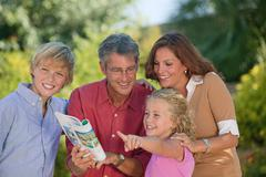 Family looking at guidebook and pointing - stock photo