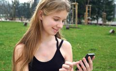 Woman using touchscreen phone outdoors in city park. Stock Photos