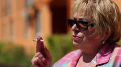 Senior woman sits on the bench and smokes a cigarette Stock Footage