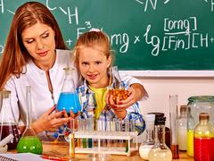 Child girl and chemistry teacher holding flask in class. - stock photo
