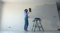 Young woman chatting on tablet while painting wall at her new home Stock Footage