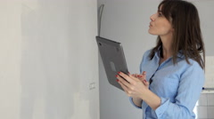Young woman painting wall and checking colour on tablet at her new home Stock Footage