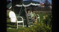 1947: Mother daughter sitting outdoor palm tree lounge chair furniture. MIAMI Stock Footage