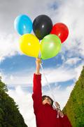 Girl holding balloons in olympic colours Stock Photos