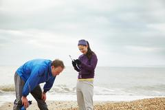 Fitness instructor with man on beach Stock Photos
