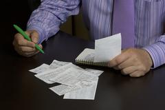 The man counts the cost of cash Cheques. A family budget Stock Photos