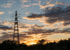 electricity transmission pylon at city suburb against the sunset glow sky. - stock photo