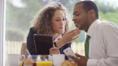 4K Attractive mixed race business couple talking & using technology at breakfast Stock Footage