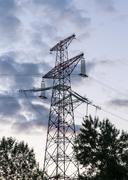 Electricity transmission pylon at city suburb against the sunset glow sky. Stock Photos