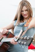 Girl playing guitar with determination - stock photo