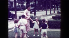 1949: Schoolmarm teacher playing kids front yard holding hands. MACON, GEORGIA Stock Footage