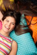 Woman lying on cushions and laughing Stock Photos