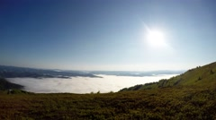 Clouds Swirling Below Green Mountain Top Under Bright Sun Stock Footage