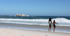 4K Young sisters playing in the water on beautiful South African beach Stock Footage
