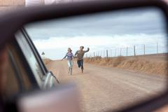 Couple running behind car - stock photo