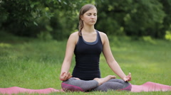 Sexy girl with a sports figure is engaged in yoga on the lawn Stock Footage