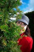 Lady peering around corner of maze - stock photo